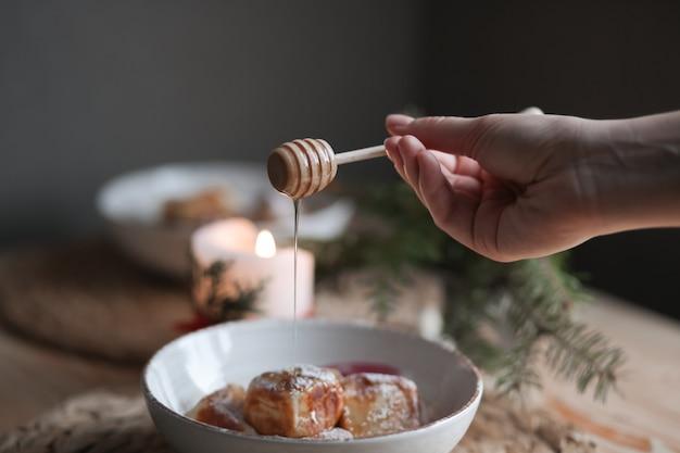 プレートに蜂蜜を注ぐスプーン。ケーキのプレート。装飾が施されたおいしい蜂蜜ケーキ。デザートの新しいデザインを作成します。