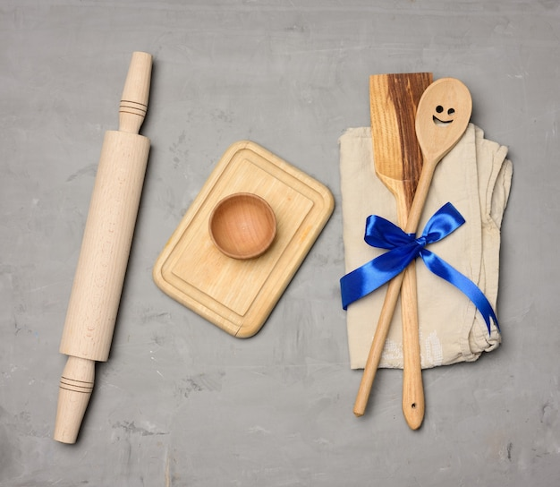 Spoon and spatula tied with blue ribbon on gray background and wooden rolling pin, top view