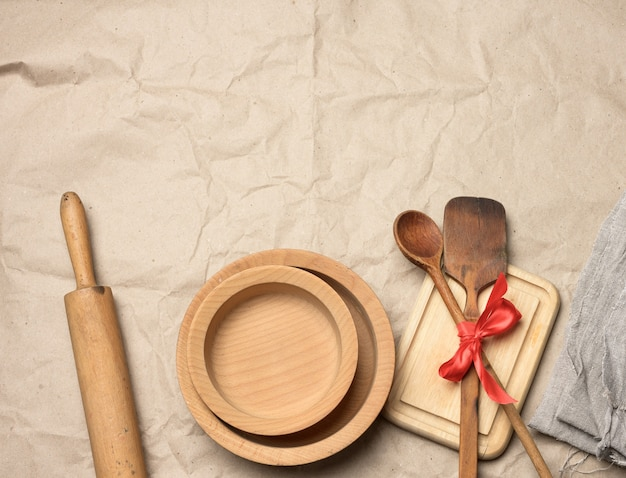 Spoon and spatula tied with red ribbon on a brown paper and wooden rolling pin, top view