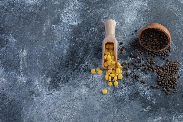 Cucchiaio di mais dolce e peperoni di grano su marmo.