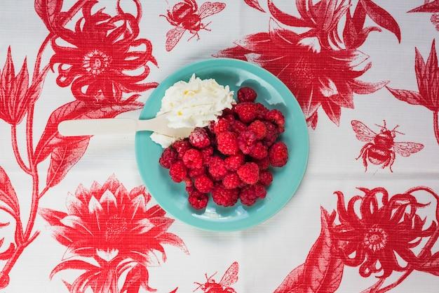 Cucchiaio in panna montata con lamponi sul piatto blu sopra la tovaglia floreale
