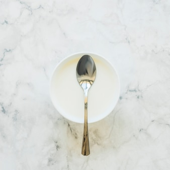 Spoon on white bowl on table