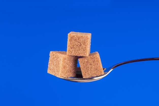 Spoon with cane sugar cubes on a blue