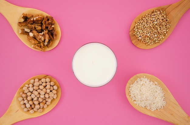 Spoon with cereals and nuts on pink background