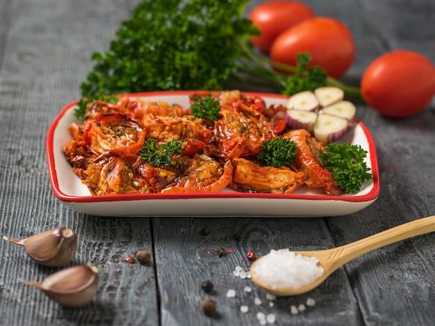 Ложка с крупной солью рядом с миской вяленых на солнце помидоров. средиземноморская закуска из томатов. вегетарианская пища.