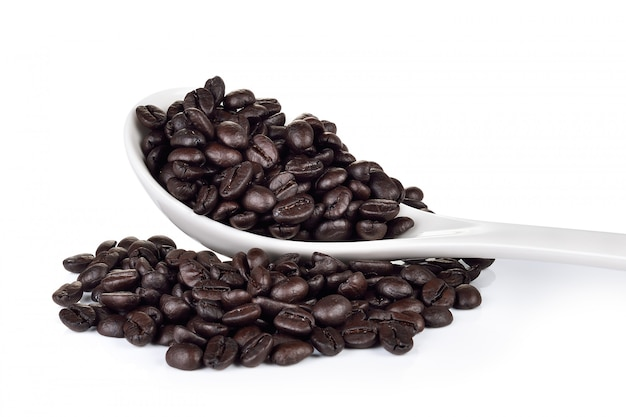 白い背景の上のコーヒー豆とスプーン