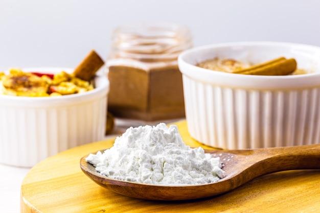 Ложка с кукурузным крахмалом, кукурузной мукой для приготовления кремов или в качестве загустителя. белая поверхность, копия пространства