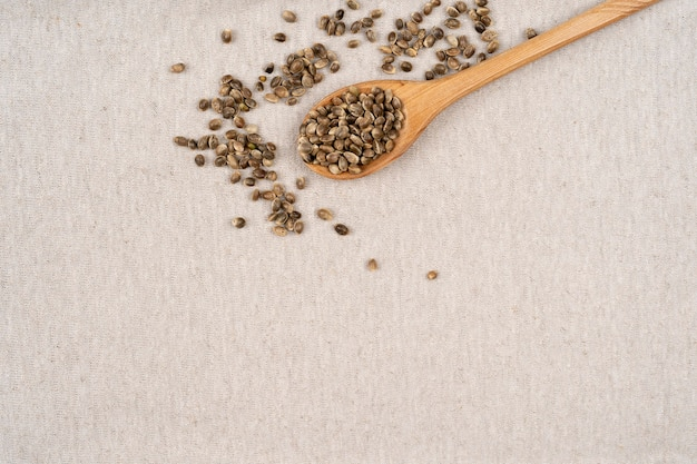 Spoon with hemp seeds on hemp textile material background hemp seeds in wooden spoon top view