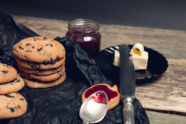 黒いテーブルの背景にチョコレートクッキーとビスケットの近くのジャムとスプーン。午後の休憩時間。朝ごはん。