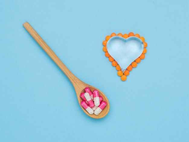 A spoon with medicinal capsules and a glass heart with pills on a blue surface