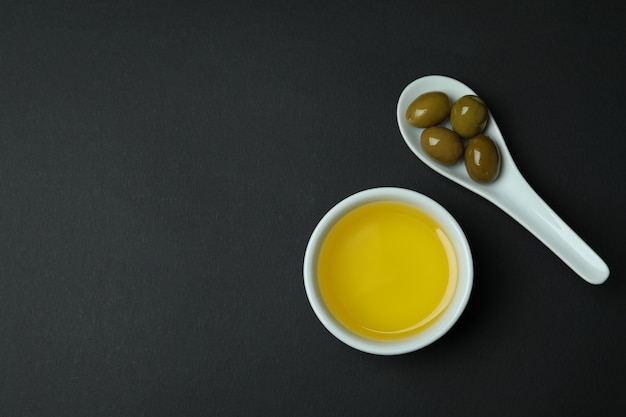Spoon with olives and bowl of oil on black surface