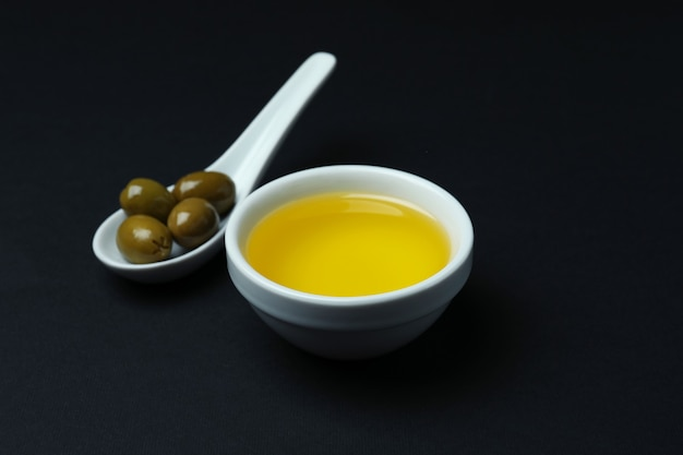 Spoon with olives and bowl of oil on black