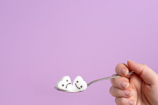 Spoon with a piece of sugar in a female hand on a lilac background.