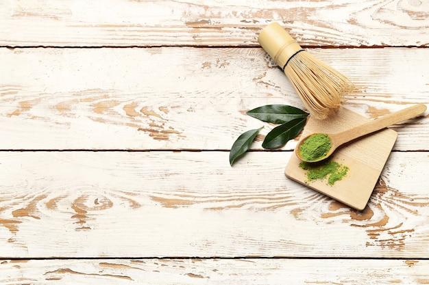 Ложка с порошкообразным чаем матча и часен на светлом деревянном фоне