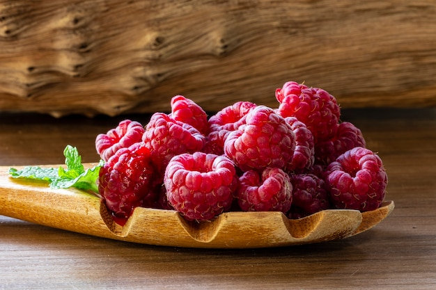 Spoon with raspberry and bowl with raspberry jam on wooden background,