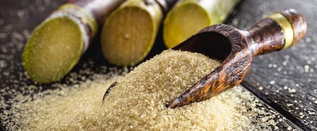 나무 바닥과 사탕수수가 있는 생 갈색 설탕을 넣은 숟가락