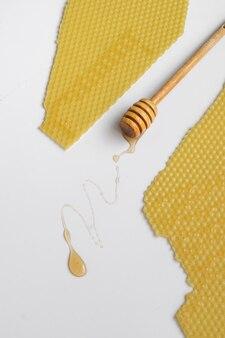 Ложка с сырым медом и пчелиным сотом на белом фоне, концепция здорового питания