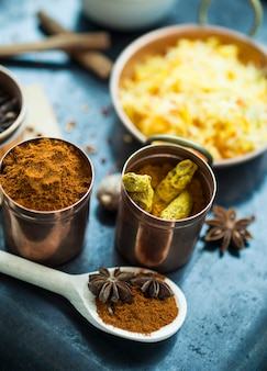 Spoon with spices near tins and dish