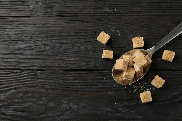 木製の背景、上面に砂糖の立方体とスプーン