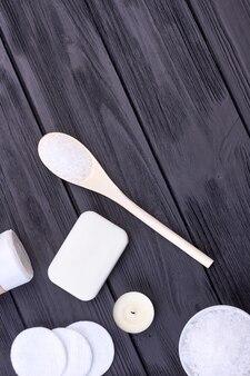 나무 책상에 흰 소금과 비누를 얹은 숟가락. 수직 샷 상위 뷰입니다. 검은 나무 배경입니다.