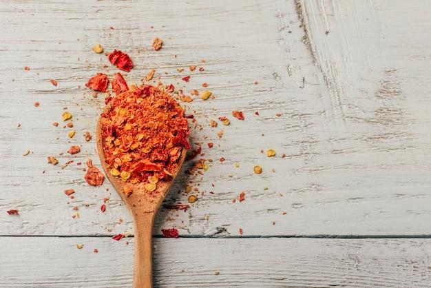 Ложка измельченного красного перца чили на деревянном фоне