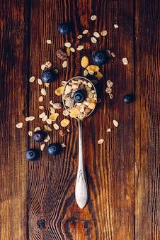 木製のテーブルにミューズリーとブルーベリーのスプーン一杯