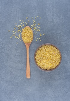 A spoonful of rice and a bowl of rice , on the marble background.