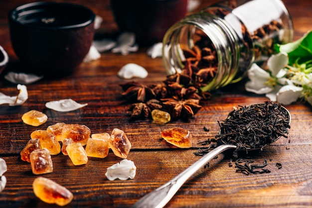 Spoonful of tea, apple flowers, sugar and scattered anise star on wooden table.