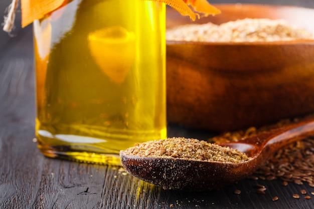 木のテーブルにガラスの水差しのspoonnd亜麻仁油に茶色の亜麻の種子。アマニ油はオメガ3脂肪酸が豊富です。