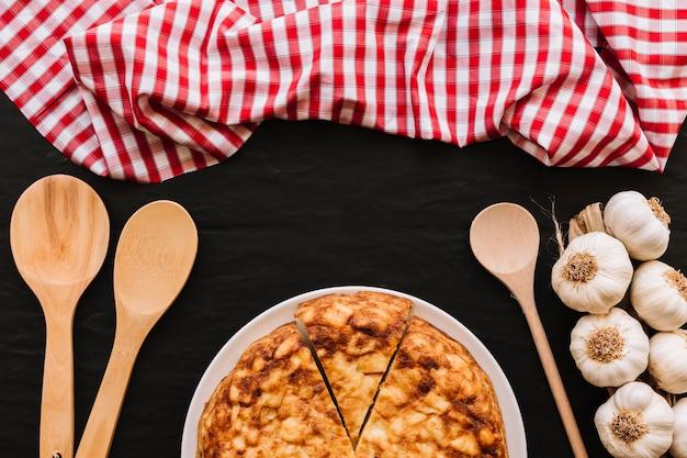 Ложки и салфетка возле чеснока и пирога