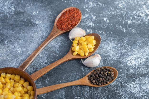Spoons of corn kernels, ground and grain peppers on marble.