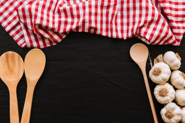 Spoons and fresh garlic near napkin