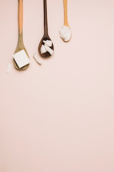 Spoons with coconut products and copy-space