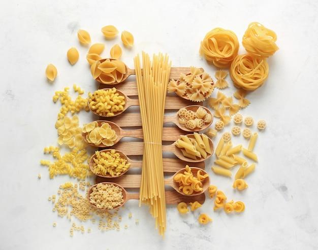 Ложки с различными видами сырых макарон на белом столе