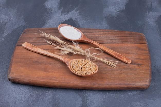 Cucchiai con spiga di grano e farina su tavola di legno.