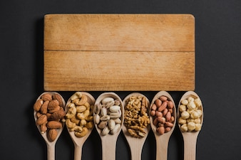 Spoons with nuts near board