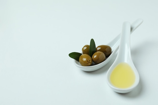 Spoons with olives and oil on white