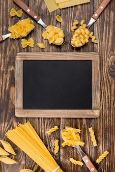 Spoons with pasta beside chalkboard