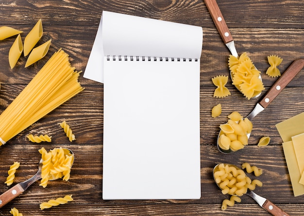 Spoons with pasta beside notebook