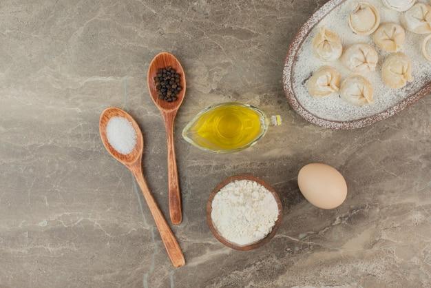 Ложки с солью, перцем, маслом, яйцом, мукой и клецками.