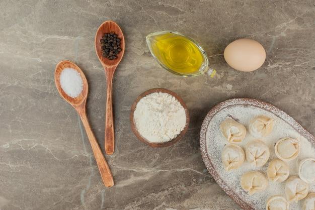 Cucchiai con sale, pepe, olio, uovo, farina e gnocchi.