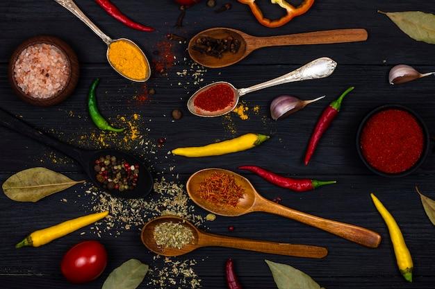 調味料とスパイス、新鮮な野菜、塩、黒の木製の背景にさまざまな色の唐辛子とスプーン。