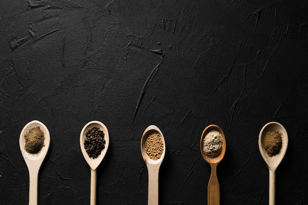 Spoons with spices on black