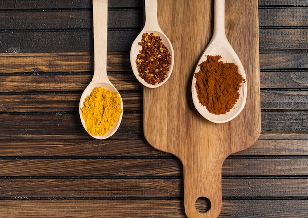 Spoons with spices and cutting board on table
