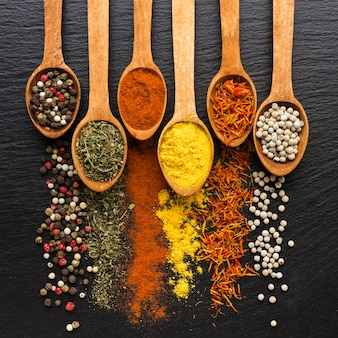 Spoons with spices powder and spread on table