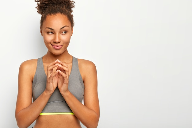 Sport and active lifestyle concept. healthy slim woman in sport clothes, keeps hands togeter,  looks thoughtfully aside, poses against white studio wall, blank space