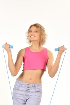 Sport, activity. smiling woman with jumping rope in her hand. attractive sport girl holding skipping rope. fitness, sport lifestyle, and health concept - woman doing sports exercises with jumping rope