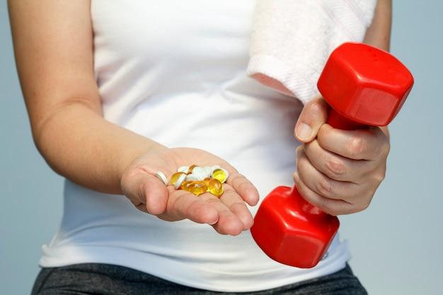 スポーツとダイエットのコンセプト-ビタミンと薬で女性の手