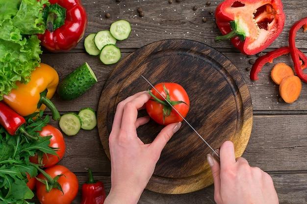 스포츠와 다이어트. 얇게 썬 야채. 후추, 토마토, 소박한 배경에 샐러드. 평면도. 공간을 복사합니다. 보드에 토마토를 자르는 손