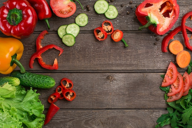 스포츠와 다이어트. 얇게 썬 야채. 후추, 토마토, 소박한 배경에 샐러드. 평면도. 복사 공간